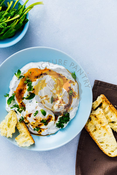 Turkish eggs served in a blue bowl drizzled with a butter sauce accompanied by spinach and toasted bread.
