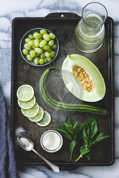 Melon, grapes, cucumber, mint, sugar, vinho verde ingredients on a baking tray.