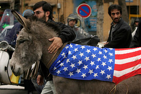 Donkeys draped in American, French, British and other western flags are led by Iranian protestors in front of the British em...