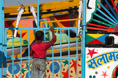 A boy peers over a fence to see a carnival ride in Pushkar, Rajasthan, India.