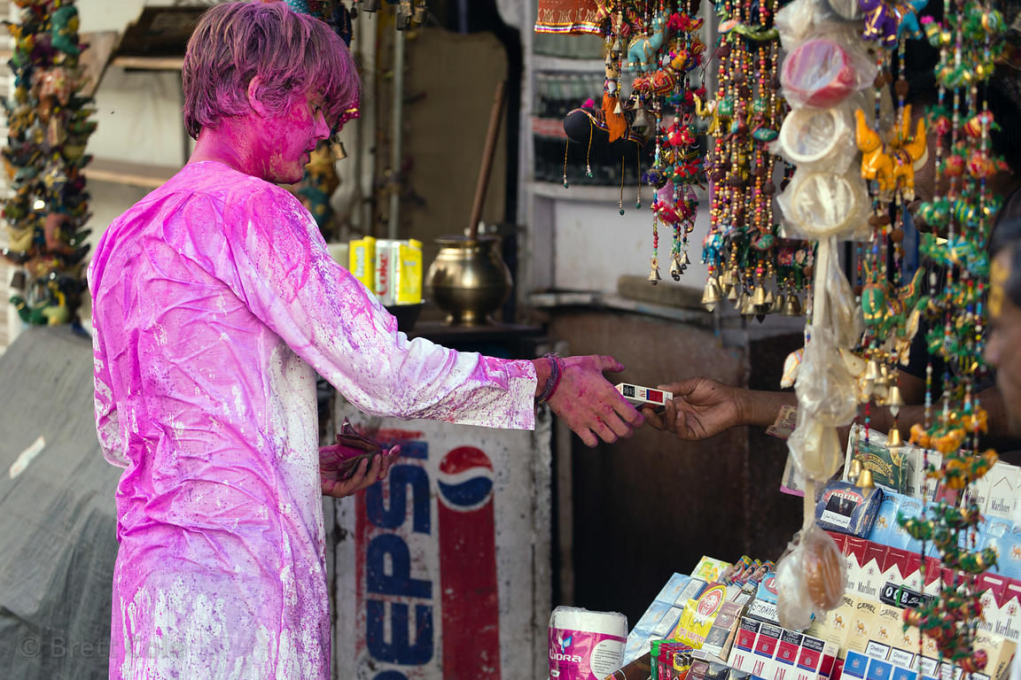 A tourist covered in gulal powder buys cigarettes during the Holi festival, Pushkar, Rajasthan, India