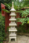 Chinese granite pagoda in the Red Wall garden planted around with palm Trachycarpus wagnerianus and Edgeworthia chrysantha. B...