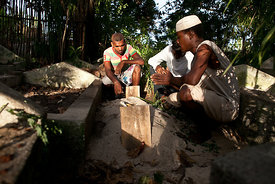 Men commune with themselves on October 7, 2013 in Nosy-Be at the grave of the eight-year-old boy whose the body was found at ...