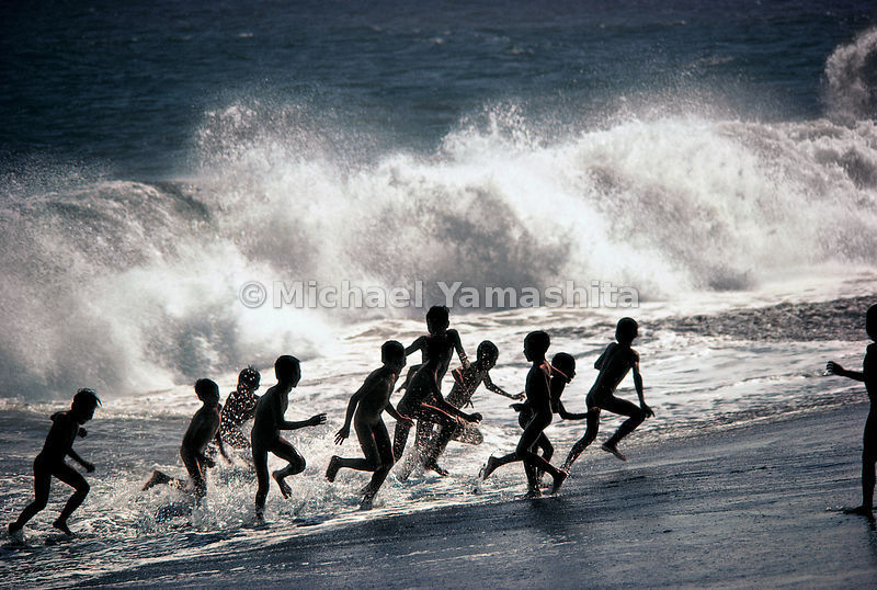 Children play in the surf on Bali beach.  Bali, Indonesia