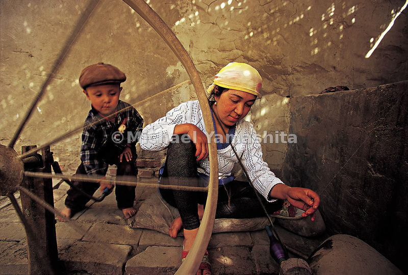A child helps his mother spin silk using a traditional large spinning wheel.