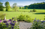 View south over surrounding farmland to distant fells from the sunny terrace planted with sun loving plants including alliums...