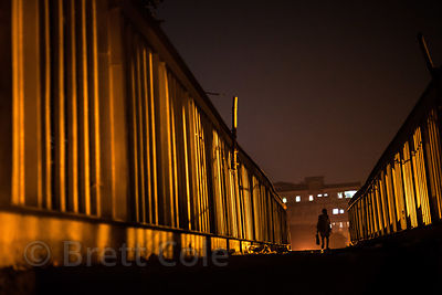 A man crosses a dramatically lit footbridge at night, over the railway tracks and busy Strand Road, near Barabazar, Kolkata, ...