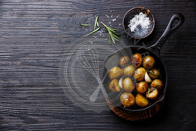 Fried baby potatoes in cast iron pan on Black Burned wooden background copy space
