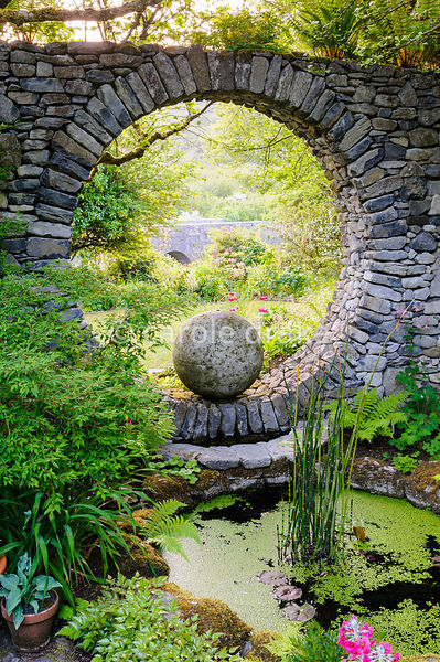 The Moon Window, a circular opening in a stone wall that echoes the arches of the bridge beyond is reflected by a circular po...