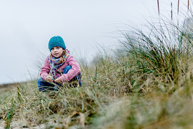 Little Danish girl in a blue hat at the beach in autumn 4