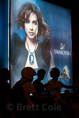 Bikers are silhouetted in front of an advert for Swarovski crystals, Mumbai, India.