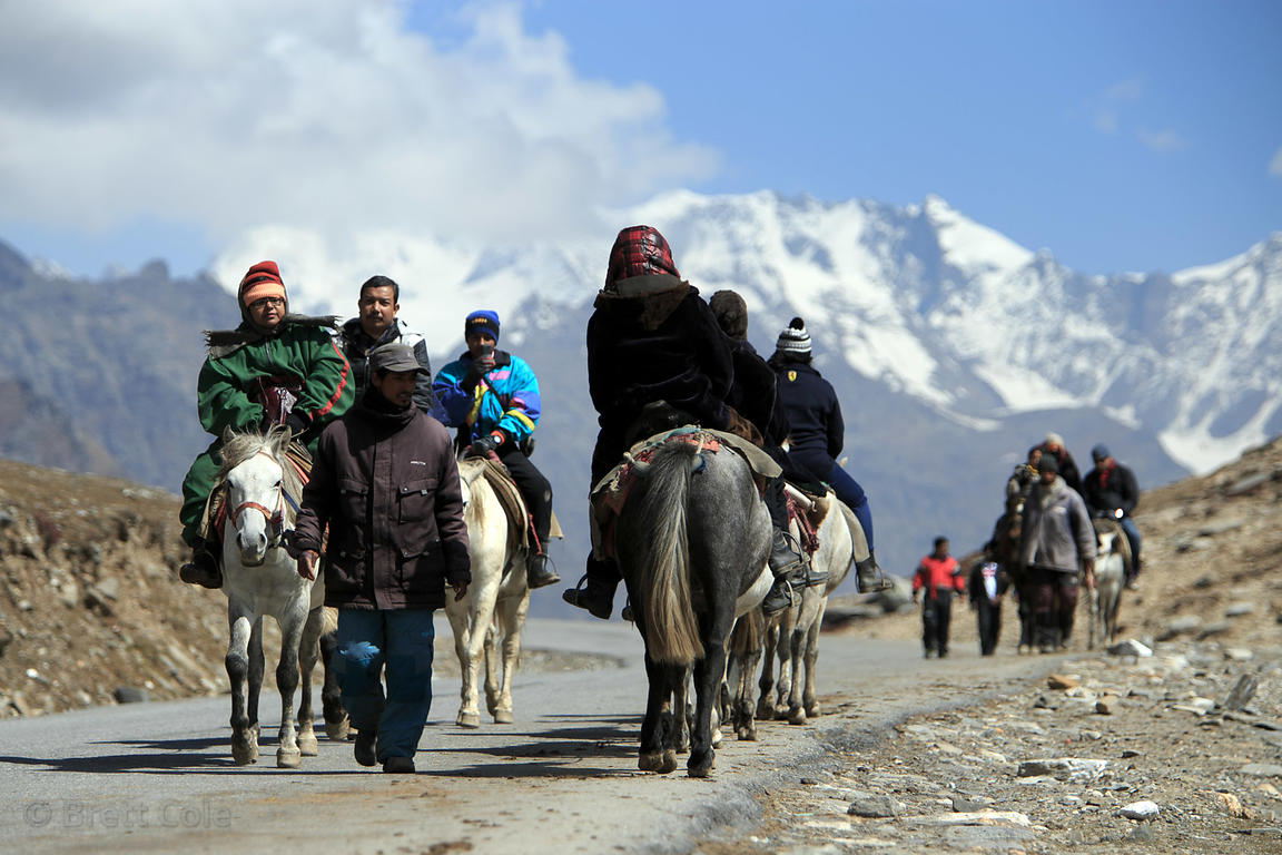 Indian tourists ride on horses while wearing rented snowsuits and fur coats, Rohtang Pass, Manali, India