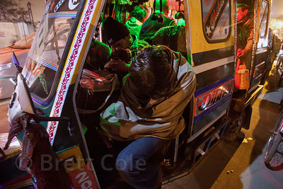 People fall asleep in an auto rickshaw while waiting for hours in gridlocked traffic at the 2013 Kumbh Mela, Allahabad, India.