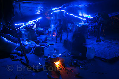 A family's tent (their home) is illuminated by blue lights during Diwali in Haridwar, India