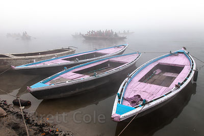 Pastel boats along the Ganges River on a foggy morning, Varanasi, India.