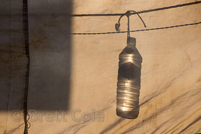 Silhouette of a plastic drinking water bottle hanging in a tent, Pushkar, Rajasthan, India