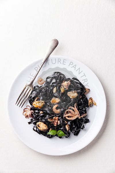 Black pasta with seafood on white plate