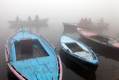 Fishing boats on a foggy winter morning along the Ganges River, Varanasi, India.