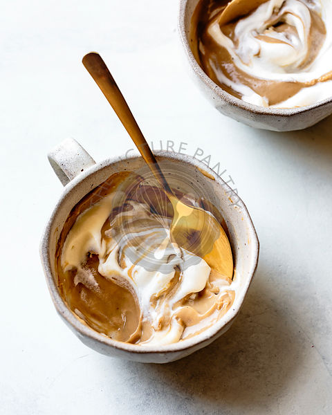 A butterscotch pudding in a cup, topped with cream.