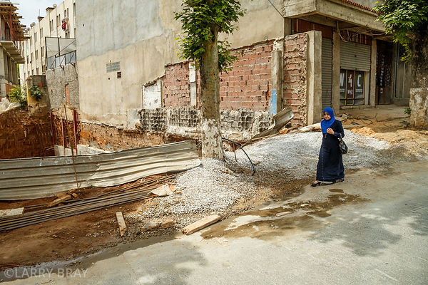 Lady walking past derelict building in Algiers, Algeria, North Africa