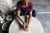 India - Rajasthan - A Potter throws clay onto a wheel to make a pot at a factory in Sanganer