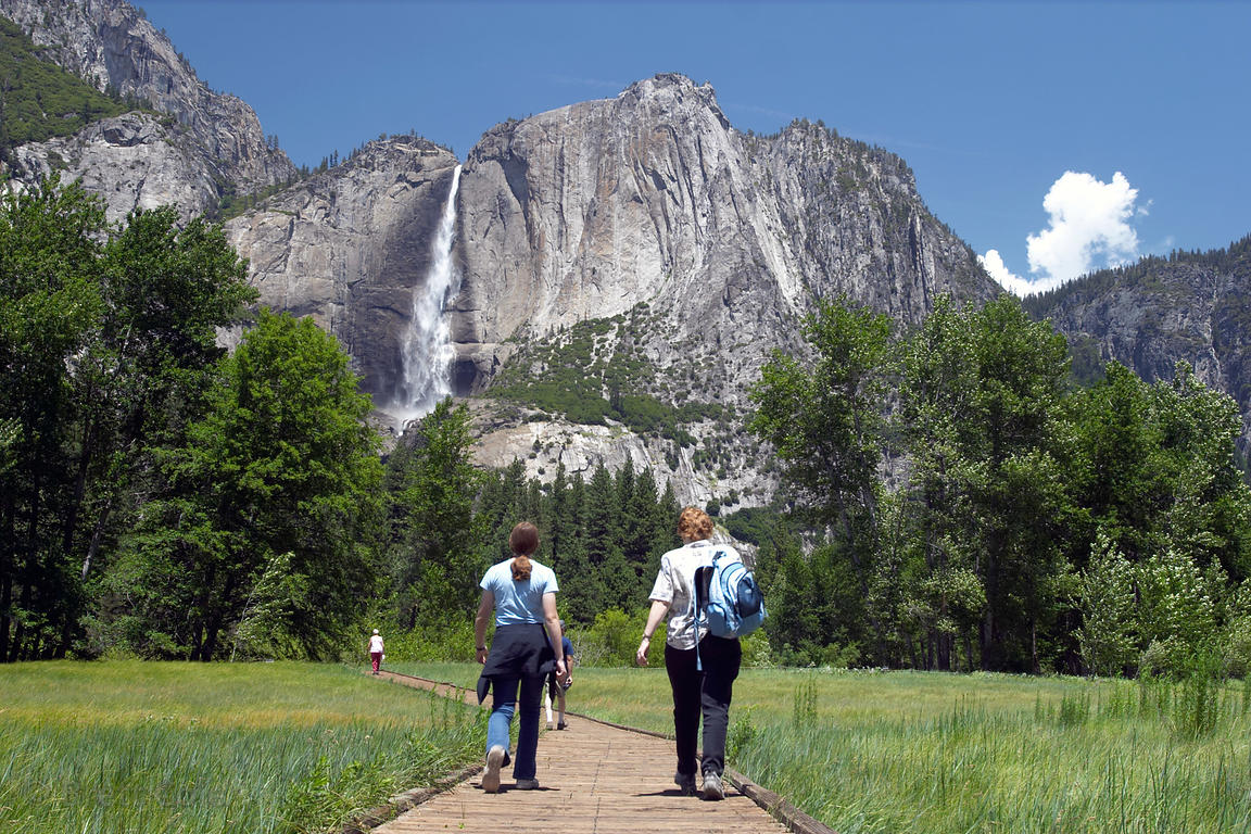 Park visitors walk along a boardwalk to view Yosemite Falls, the tallest waterfall in the US. Yosemite National Park, Califor...