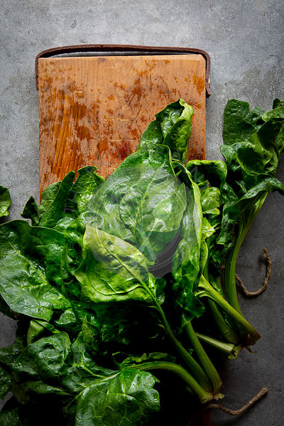 Fresh Spinach on wooden board over grey concrete background