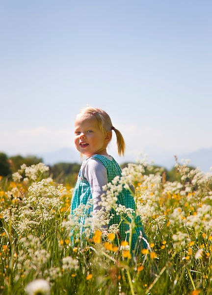 Girl walking in field of flowers