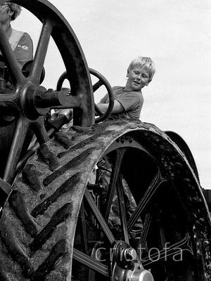 a young boy drives a traction engine at the St Agnes Steam Fair