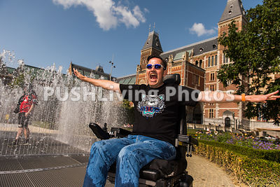 Man using a power wheelchair enjoying a fountain