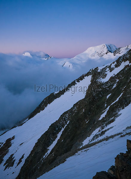 The snow capped summit of Alphubel standing out against the pink and blue dawn sky over Saas Fee in the Alps.