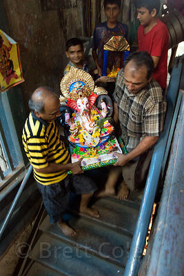A family carries their Ganpati (Ganesh idol) from their home to a truck, in preparation to immerse it in the Arabian Sea at C...
