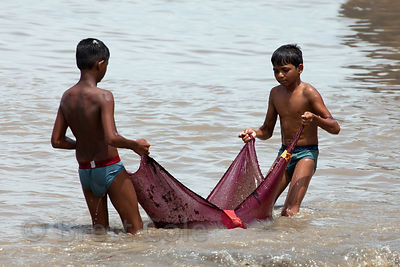 Boys from the Colaba fishing village in Mumbai, India haul in a net full of garbage. The boys bring the net back and dump it ...