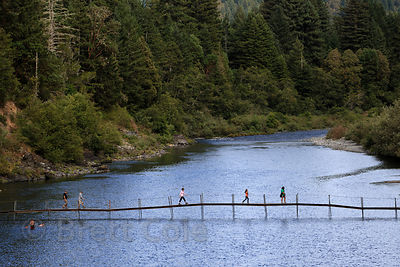 Hikers walk over seasonal footbridge over the Smith River, Jedidiah Smith Redwoods State Park, California. The bridge is erec...