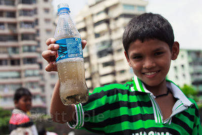 A boy holds up a bottle of murky water from the Arabian Sea, in the fishing village of Colaba, Mumbai, India.