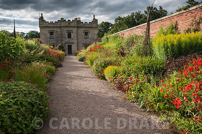 Hot border full of reds, oranges and yellows, including alstroemeria, persicaria, crocosmia, achillea and solidago. Floors Castle, Kelso, Roxburghshire, Scotland