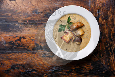 Cream soup with porcini mushroom on wooden table copy space