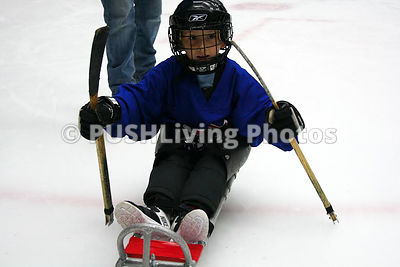 Young boy playing sled hockey