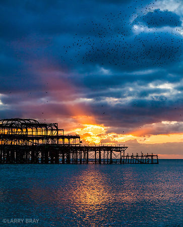 West Pier with blue wintery sky and sea with orange rays of sunlight in Brighton, East Sussex, UK