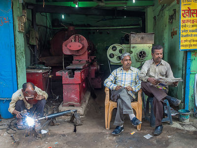 A worker welds while others take a break, in a workshop in Gujarat