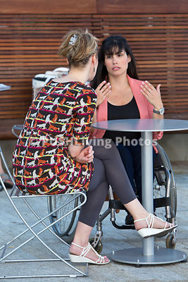 Woman in a wheelchair in a cafe with her friend