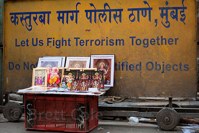 Ganesh prints for sale, in front of a security sign, during the Ganesh Chaturthi festival, Lalbaug, Mumbai, India.