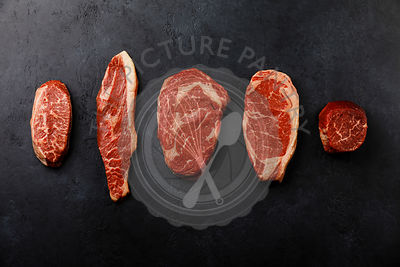 Variety of Raw Black Angus Prime meat steaks Top Blade,  Top sirloin cap, Rib Eye, Striploin, Tenderloin fillet Mignon on dar...