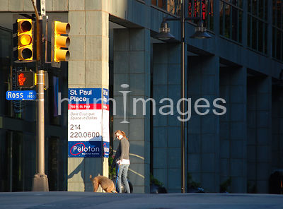 Woman walking dog in downtown area of an American city