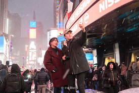 Tourists taking selfies on a snowy day at Times Square in New York City