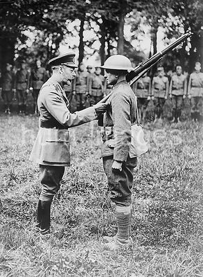 King George V of Great Britain (1865-1936) giving a medal to an American soldier in France during World War I.
