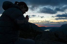 A woman praying to God on the summit of a mountain.