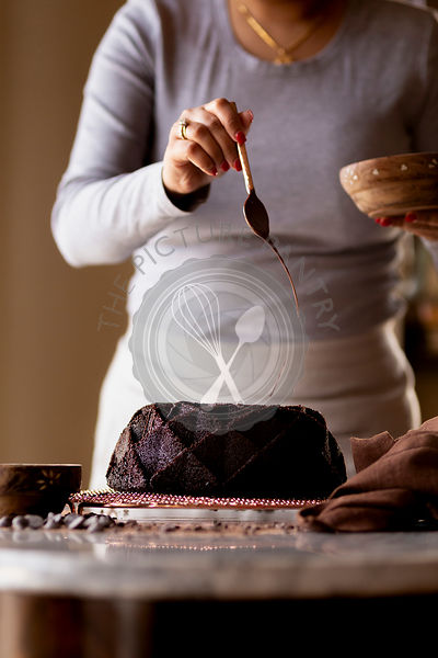 A woman decorating a Gluten-free Chocolate Budnt cake with chocolate drizzle.