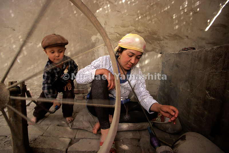 A young Uygur mother gets an assist from her industrious son, as they spin silk fibers on a wheel, just as their ancestors did when Silk Road traders stopped here to buy fabrics and other goods.  Hotan, Xinjiang, China