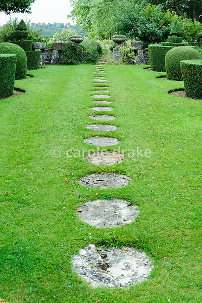 Circular stone paving slabs form a path across the lawn of the Topiary Garden. Rodmarton Manor, Rodmarton, Tetbury, Glos, UK